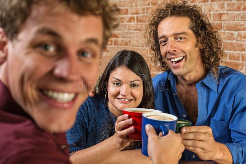Amigos que tuestan con las tazas de café fotos de archivo libres de regalías