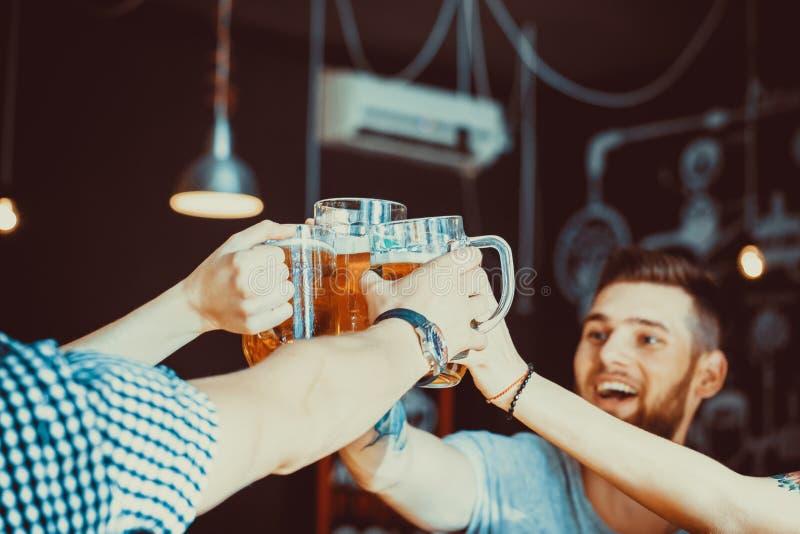 Amigos que tuestan con los vidrios de cerveza ligera en el pub imagenes de archivo