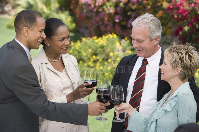 Amigos que tuestan el vino junto imagenes de archivo