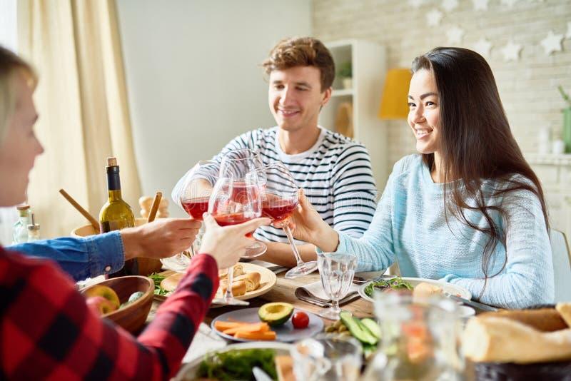 Amigos que tuestan en la cena de la acción de gracias imágenes de archivo libres de regalías