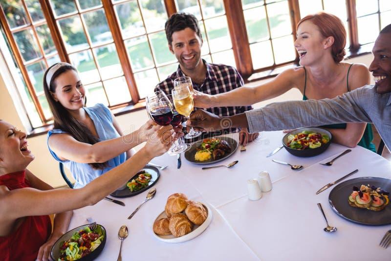 Amigos que tuestan la copa de vino en la tabla en restaurante imagen de archivo