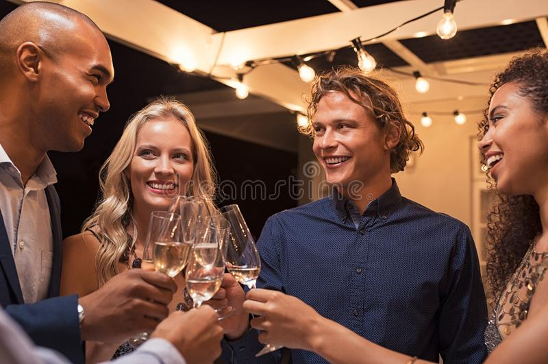 Amigos que tuestan los vidrios del champán fotografía de archivo