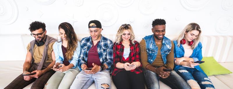 Amigos que usam o smartphone no sofá no local de encontro interno - pessoa agrupe viciado pelo telefone esperto móvel - conceito  imagem de stock