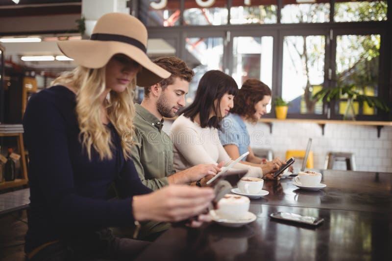 Amigos que usam telefones celulares ao sentar-se com os copos de café no café imagem de stock
