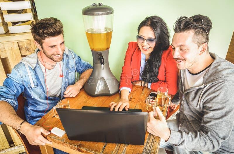 Amigos que usan el ordenador portátil del ordenador en la barra de la cervecería - comunidad conectada de gente joven de los estu foto de archivo