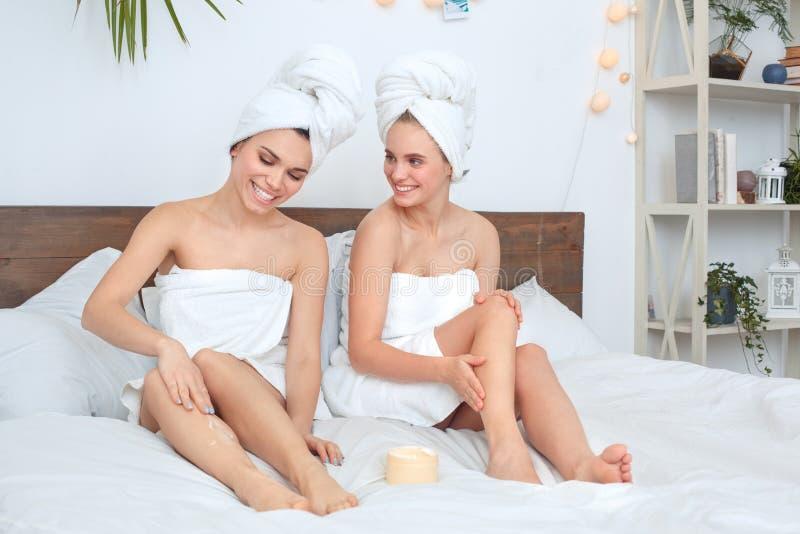 Amigos que vestem o cuidado da beleza de toalhas junto em casa que encontra-se aplicando a fala da loção do corpo alegre imagens de stock royalty free