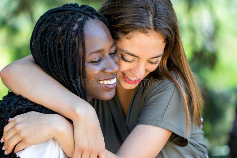 Amigos raciais diversos que abraçam fora fotos de stock royalty free