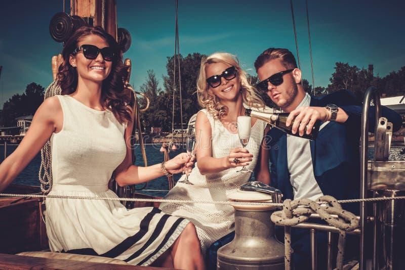 Amigos ricos elegantes que se divierten en un yate de lujo imagen de archivo