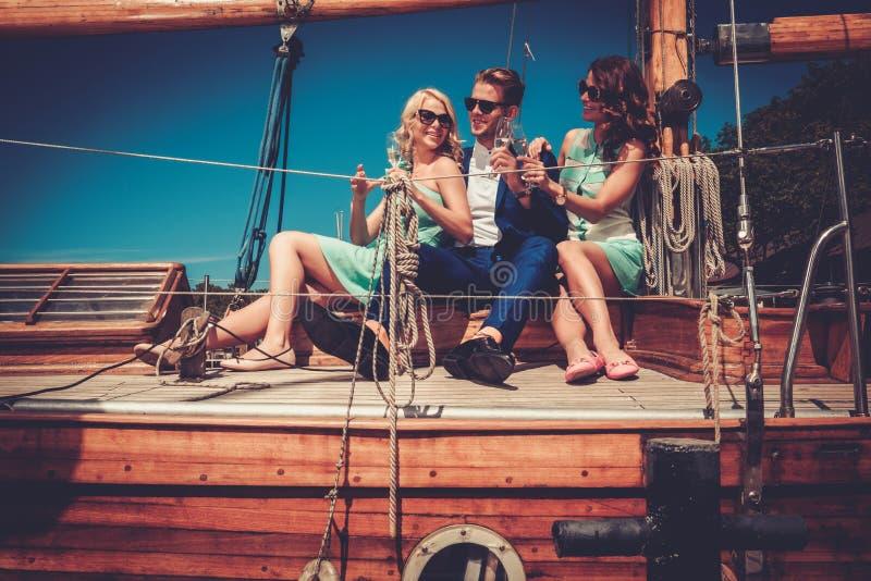 Amigos ricos elegantes que se divierten en un yate de lujo fotografía de archivo libre de regalías