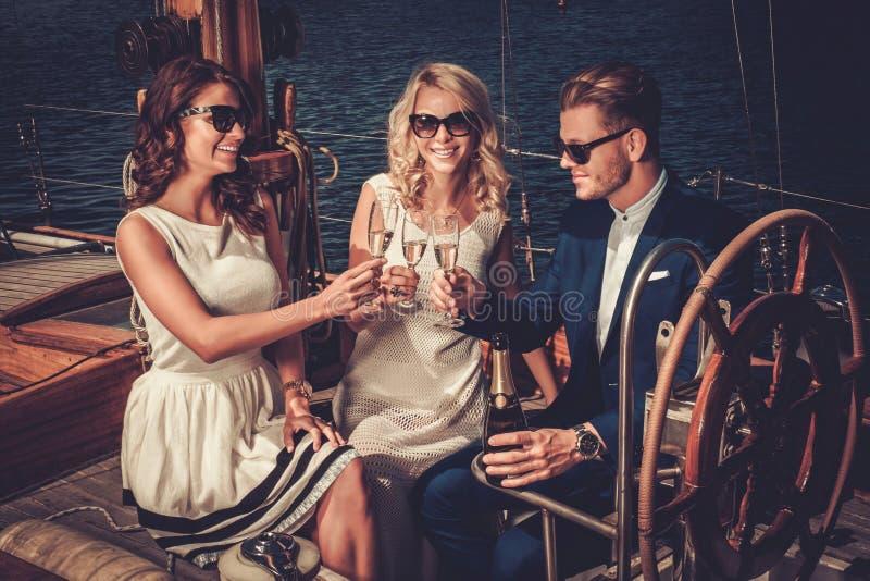 Amigos ricos elegantes que se divierten en un yate de lujo fotos de archivo libres de regalías
