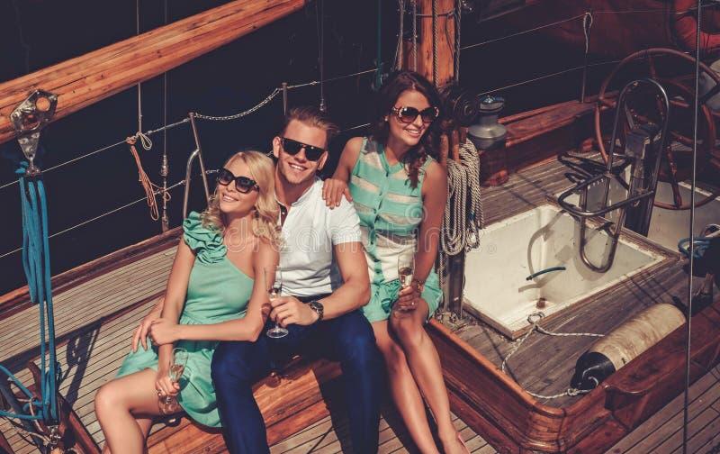 Amigos ricos elegantes que se divierten en un yate de lujo fotografía de archivo