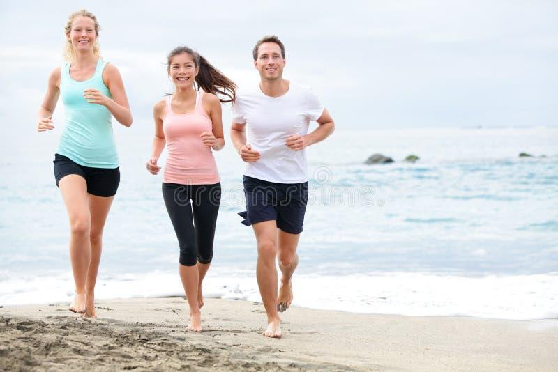 Amigos running em movimentar-se da praia fotos de stock royalty free