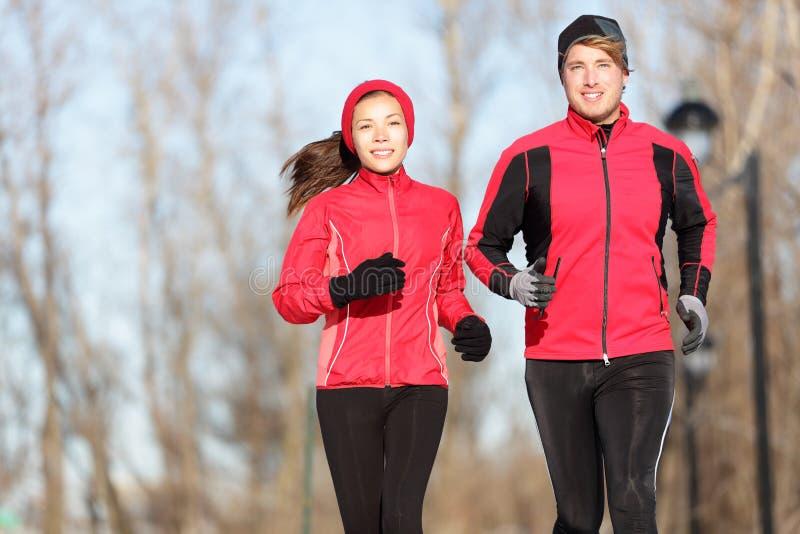 Amigos Running no inverno imagens de stock royalty free