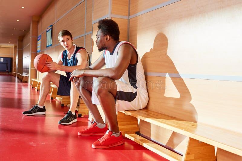 Amigos sérios do basquetebol que compartilham de expressões do jogo foto de stock