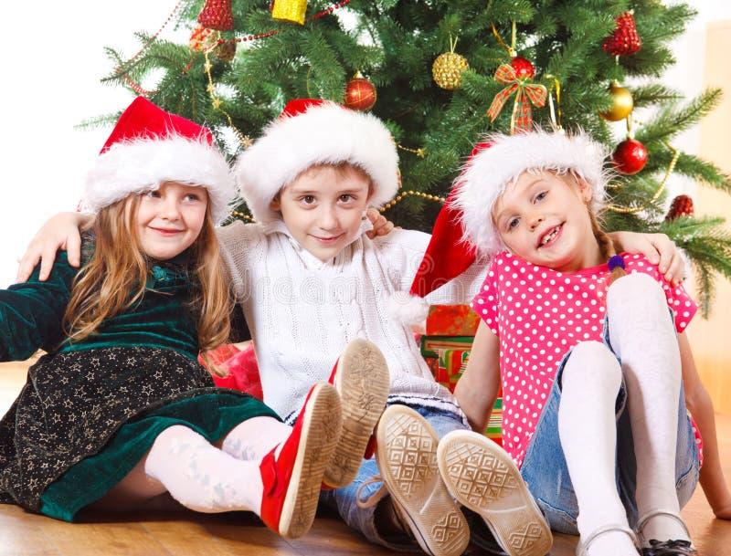 Amigos sob a árvore de Natal foto de stock royalty free