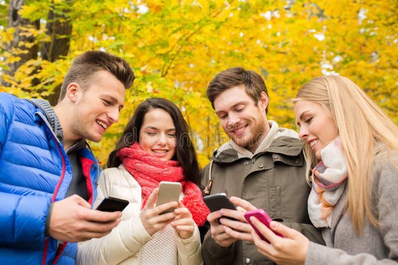 Amigos sonrientes con smartphones en parque de la ciudad fotos de archivo libres de regalías