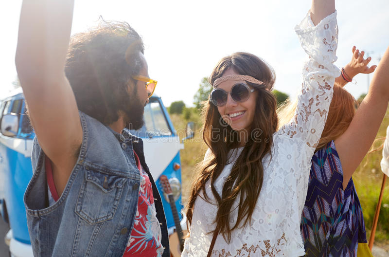 Amigos sonrientes del hippie que se divierten cerca del coche del minivan imagen de archivo libre de regalías