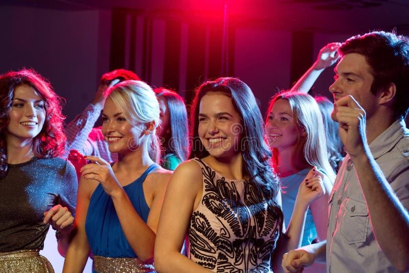 Amigos sonrientes que bailan en club imágenes de archivo libres de regalías