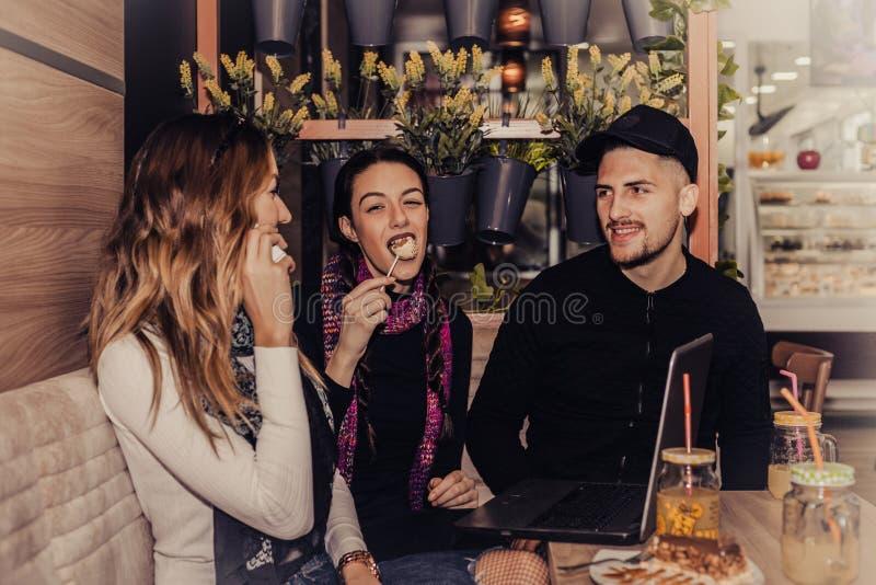 Amigos sonrientes que beben el café y usar el ordenador portátil en la cafetería imagen de archivo