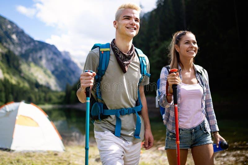 Amigos sonrientes que caminan con las mochilas Avent?rese, viaje, turismo, alza y concepto de la gente foto de archivo libre de regalías