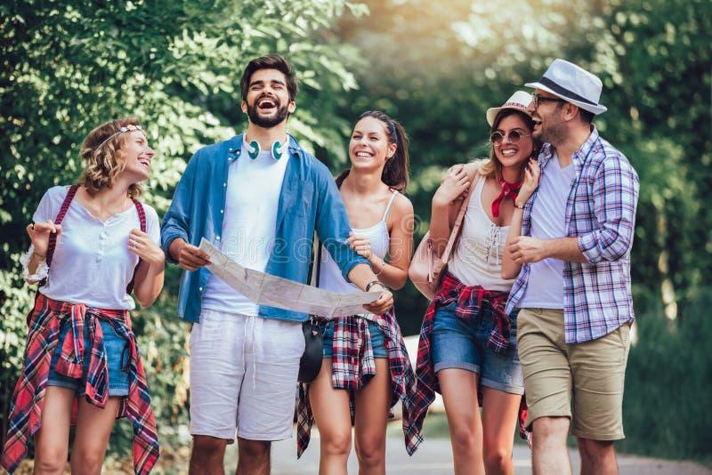 Amigos sonrientes que caminan con las mochilas en el bosque - aventura, viaje, turismo, alza y concepto de la gente imágenes de archivo libres de regalías