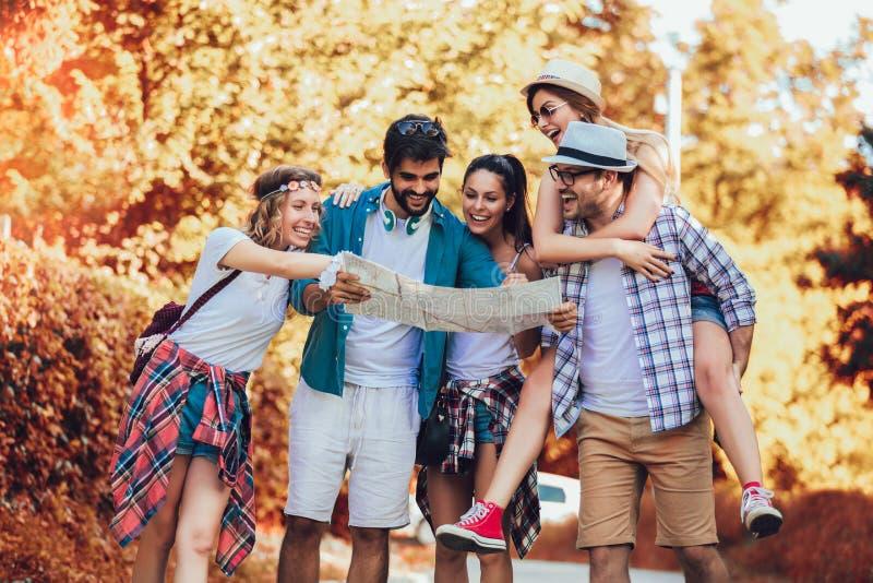 Amigos sonrientes que caminan con las mochilas en el bosque - aventura, viaje, turismo, alza y concepto de la gente fotografía de archivo libre de regalías