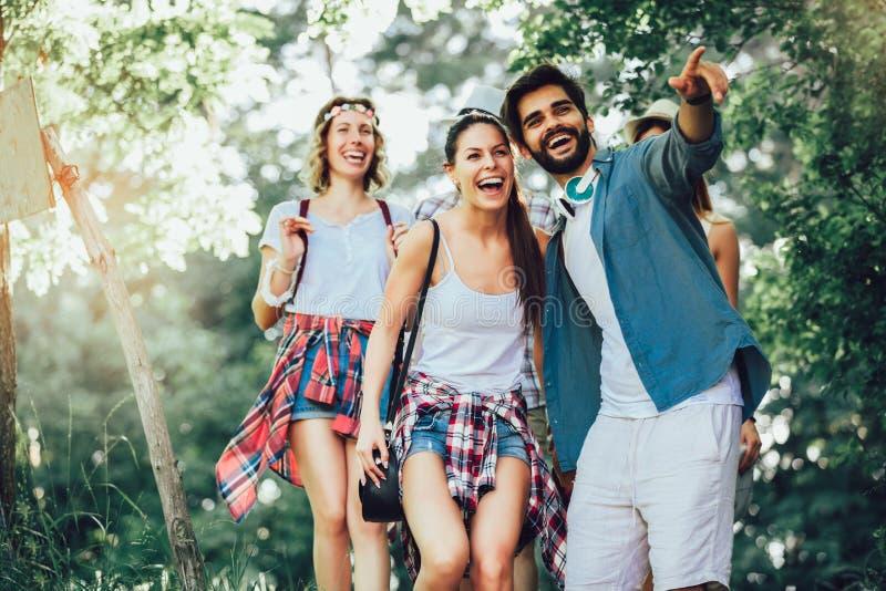 Amigos sonrientes que caminan con las mochilas en el bosque - aventura, viaje, turismo, alza y concepto de la gente imagen de archivo