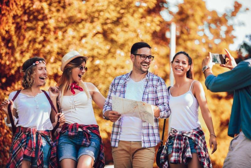 Amigos sonrientes que caminan con las mochilas en el bosque - aventura, viaje, turismo, alza y concepto de la gente foto de archivo libre de regalías