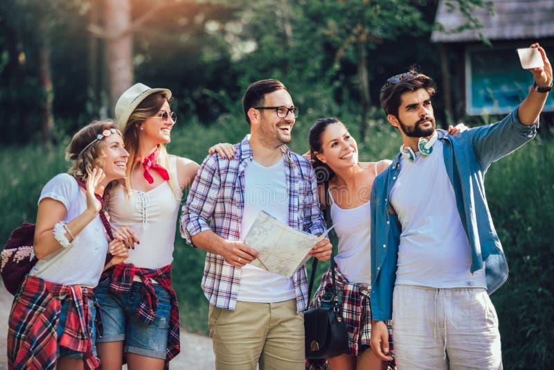 Amigos sonrientes que caminan con las mochilas en el bosque - aventura, viaje, turismo, alza y concepto de la gente imagen de archivo libre de regalías
