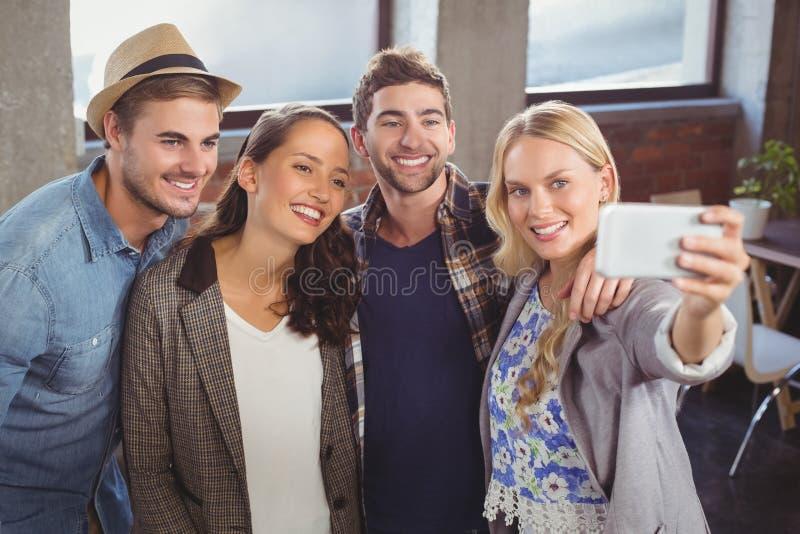 Amigos sonrientes que colocan y que toman selfies foto de archivo libre de regalías