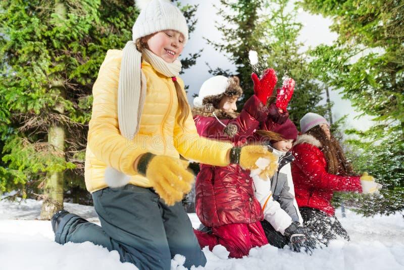 Amigos sonrientes que juegan con nieve en bosque del invierno foto de archivo libre de regalías