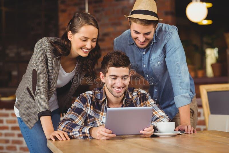 Amigos sonrientes que miran la tableta foto de archivo