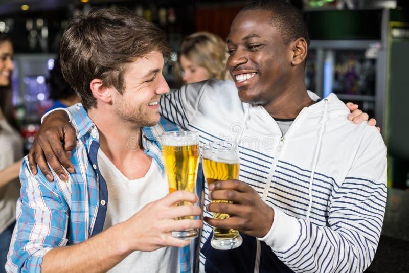 Amigos sonrientes que prueban con la cerveza con sus amigos imagen de archivo