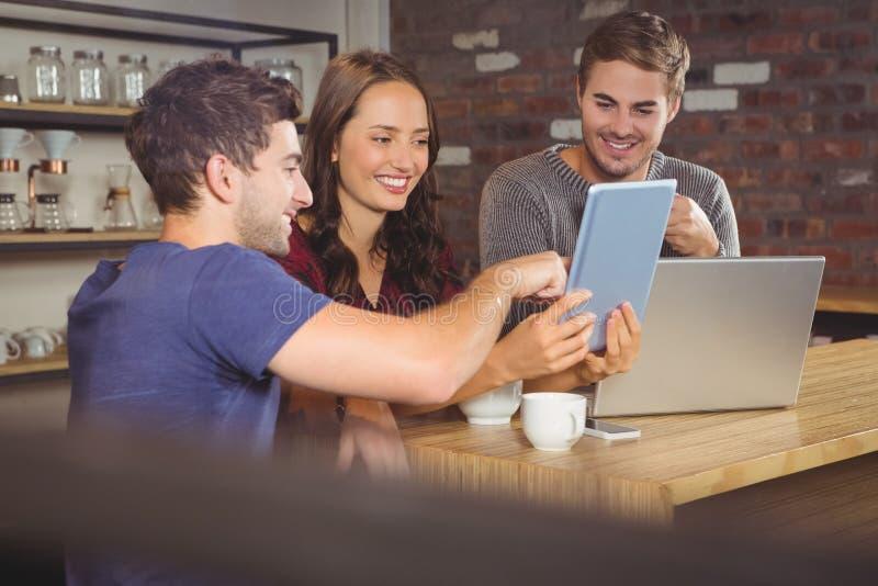 Amigos sonrientes que señalan y que miran la tableta imagen de archivo