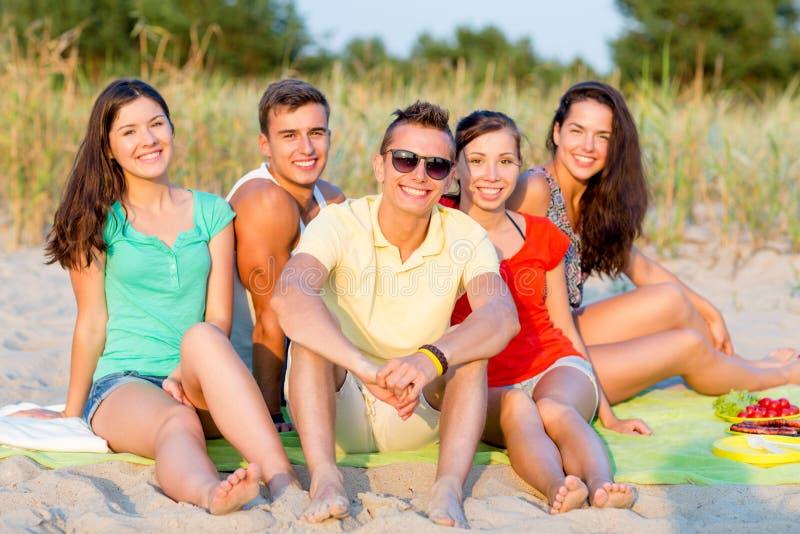 Amigos sonrientes que se sientan en la playa del verano fotos de archivo
