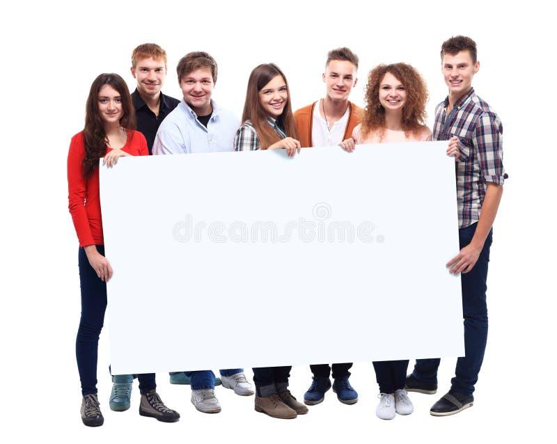 Amigos sonrientes que sostienen la bandera en blanco foto de archivo libre de regalías