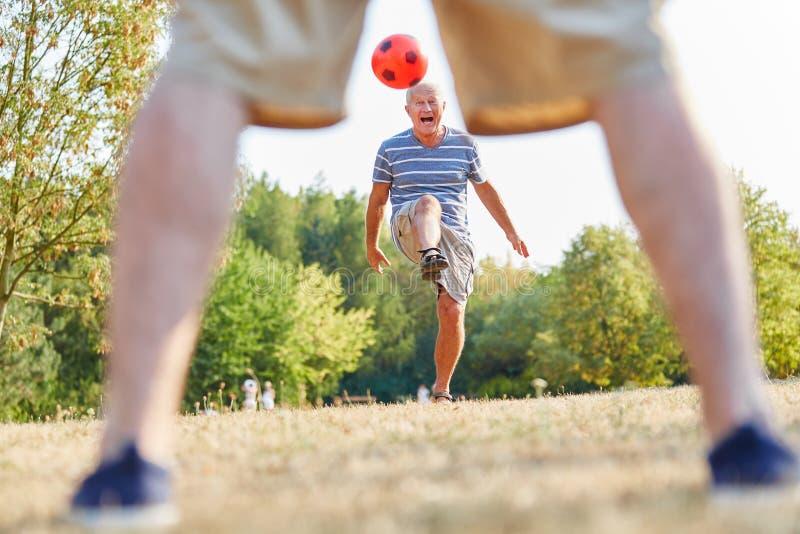 Amigos superiores ativos que jogam o futebol fotografia de stock royalty free