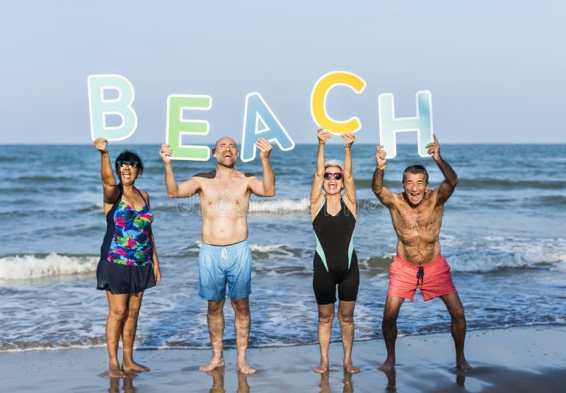 Amigos superiores que apreciam a praia no verão foto de stock royalty free