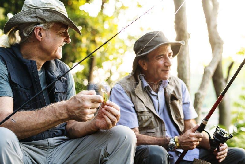 Amigos superiores que pescam pelo lago imagens de stock royalty free