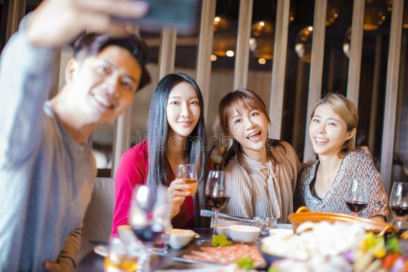 Amigos tomando selfie en el restaurante caliente foto de archivo