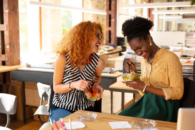 Amigos trabalhando juntos rindo enquanto almoçam foto de stock royalty free
