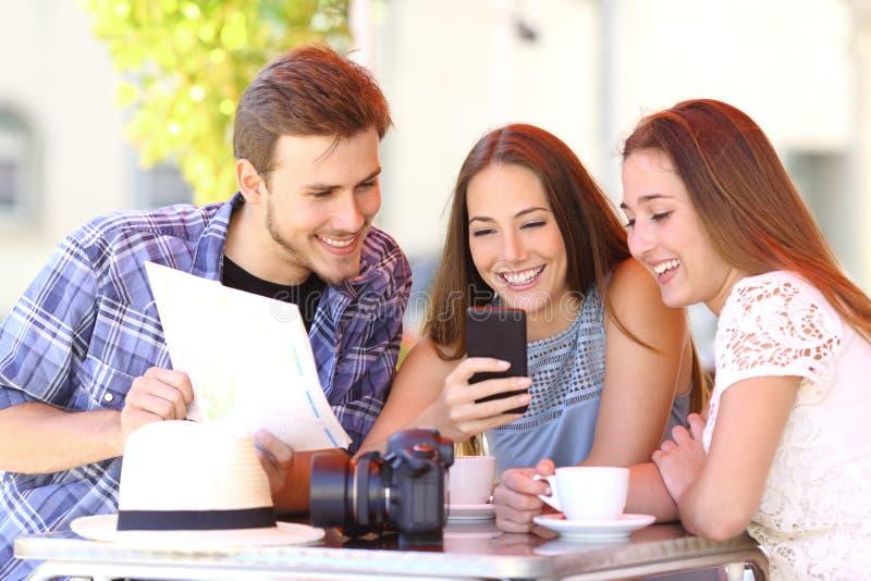 Amigos turísticos que planean vacaciones con el teléfono de los gps imagen de archivo