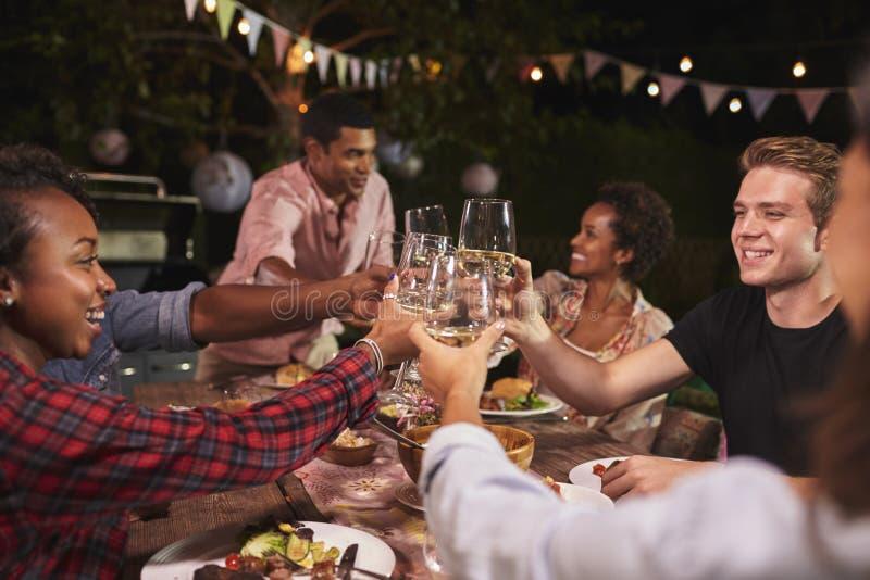 Amigos y familia que tuestan en el partido de cena del jardín, cierre para arriba fotos de archivo libres de regalías