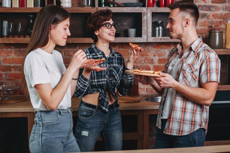 Amigos y pizza Tres personas alegres jovenes que comen la pizza, lau imagen de archivo libre de regalías