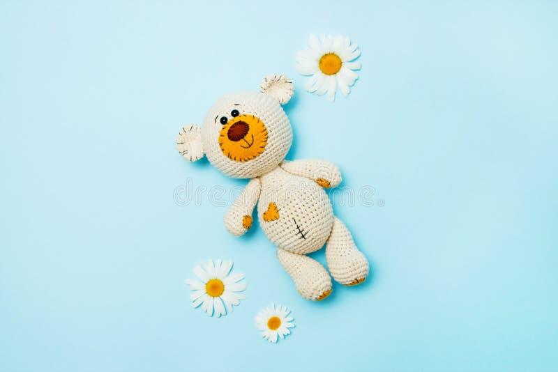 Amigurumi handmade miś z stokrotkami odizolowywać na błękitnym tle dziecka t?a kopii przestrzeni tekst Odbitkowa przestrze?, odg? zdjęcie stock