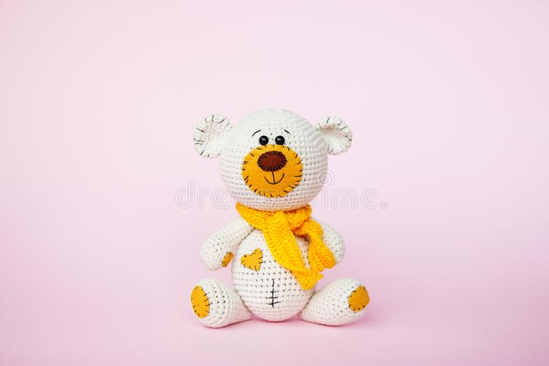 Amigurumi handmade teddy bear isolated on a pink background. Baby background. Copy space royalty free stock images