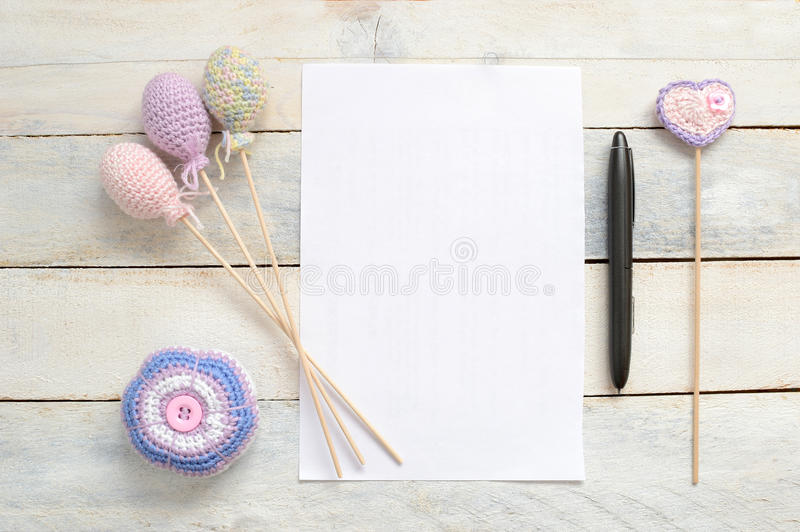 Amigurumi, Inspirational white card with some crochet handmade decoration. Inspirational white blank card with some crochet handmade decoration on a white wooden royalty free stock image