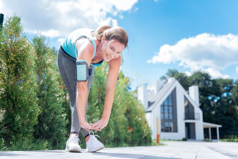 Amincissez et adaptez la femme aux cheveux blonds étirant ses jambes après course de matin photo stock
