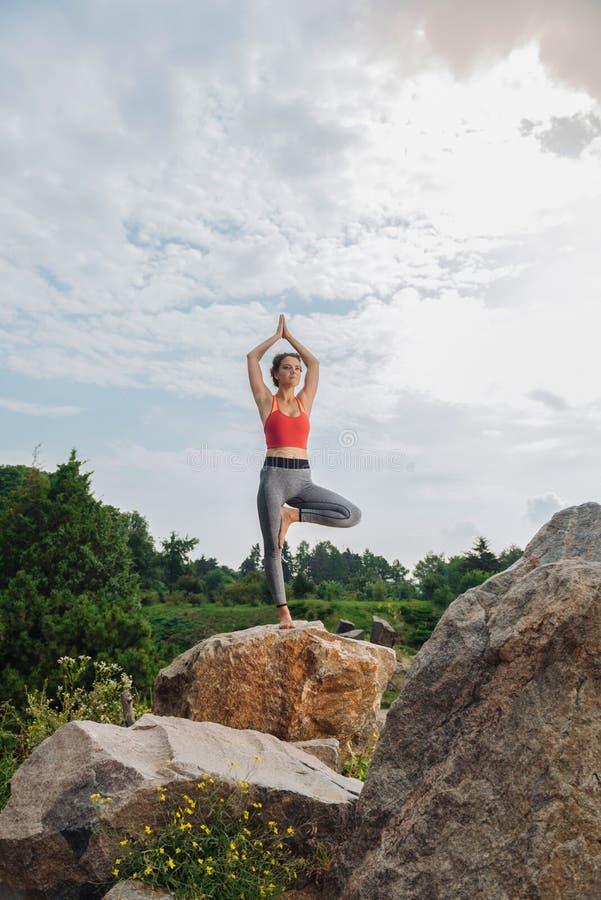 Amincissez et adaptez la femme se sentant paisible tout en faisant la pose de yoga photos stock