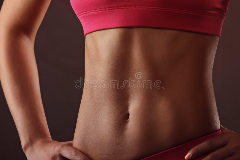 Amincissez le corps de la femme bronzée au-dessus du fond gris-foncé photo libre de droits